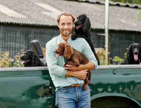 James Middleton leaning against Land Rover truck holding one of his dogs