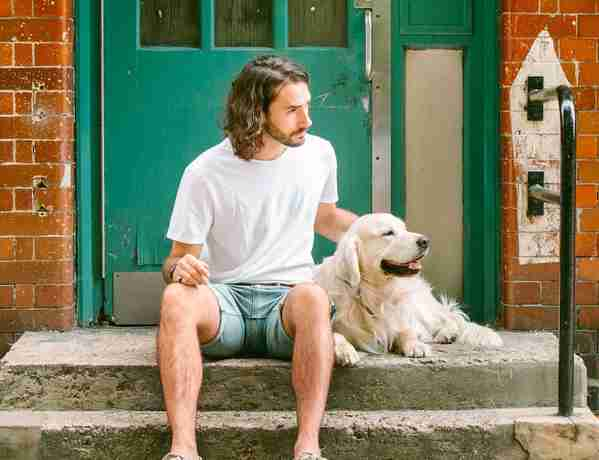 Waggel Co-founder Ross Fretten sits on steps with his Golden Retriever Sailor